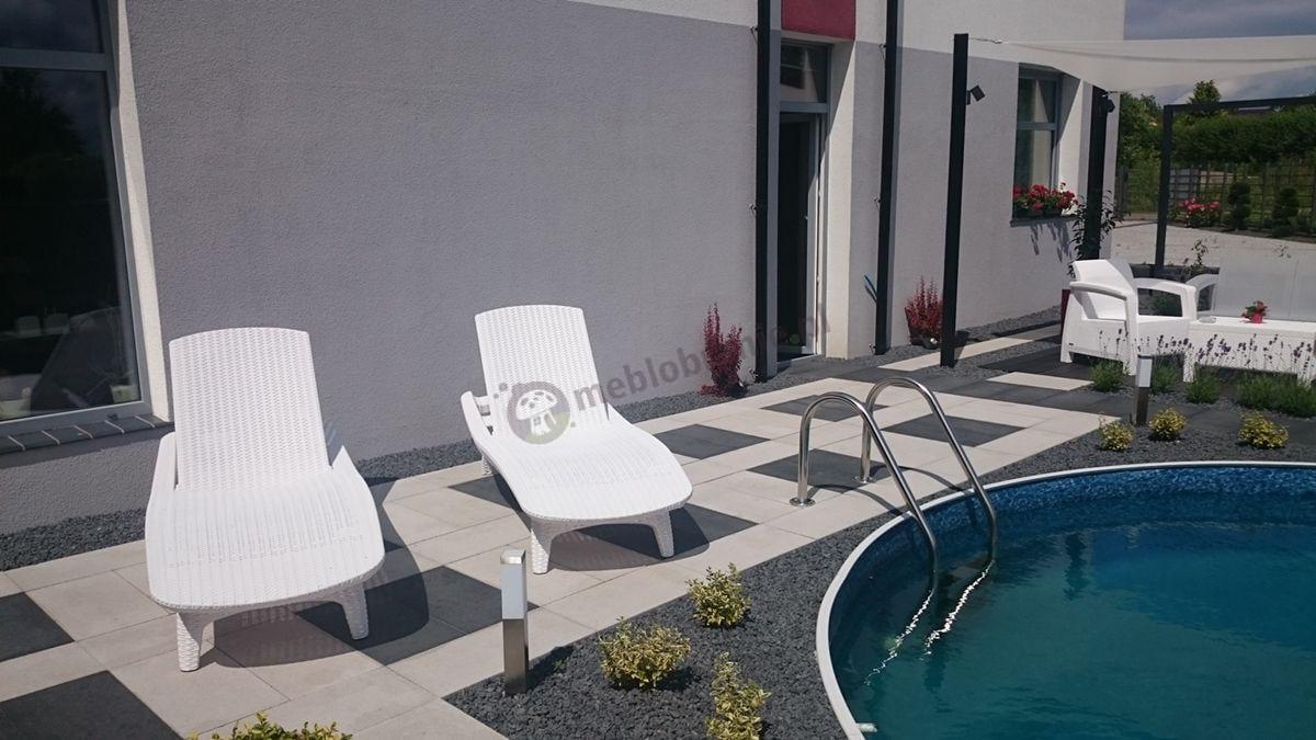 Białe leżaki ogrodowe nad eleganckim basenem
