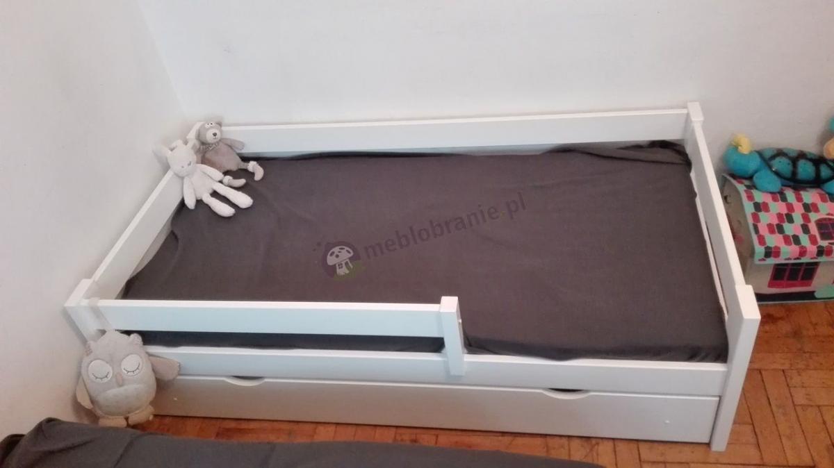Białe łóżeczko dziecięce drewniane z szufladą w pokoju dziecięcym