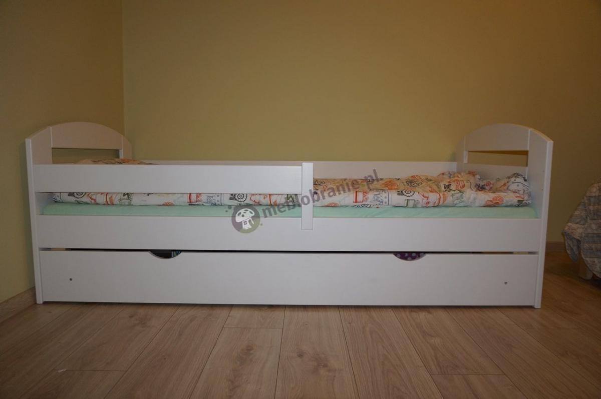 Białe łóżko z barierką dla dziecka w pastelowym pokoju