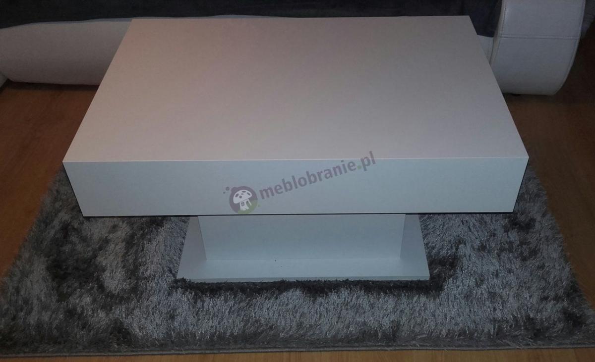 Biały stolik do salonu ustawiony na srebrnym dywanie