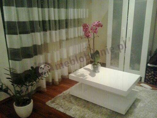 Biały stolik kawowy do salonu ozdobiony orchideą