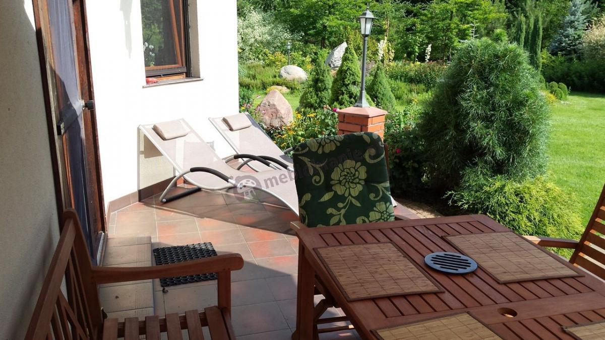 Brązowe leżanki do ogrodu z poduszkami i podłokietnikami