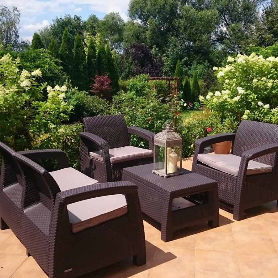 Brązowe meble ogrodowe Allibert Keter Corfu Set w pełnym zieleni ogrodzie