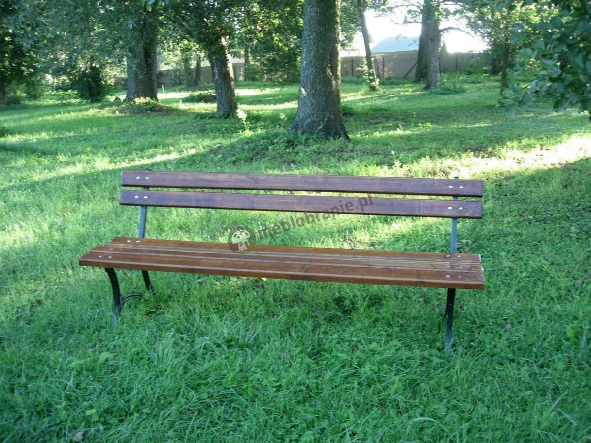 Ciemna ławka ogrodowa z drewna ustawiona na trawniku