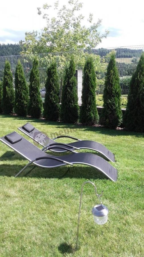 Czarne leżanki ogrodowe ustawione przy latarence