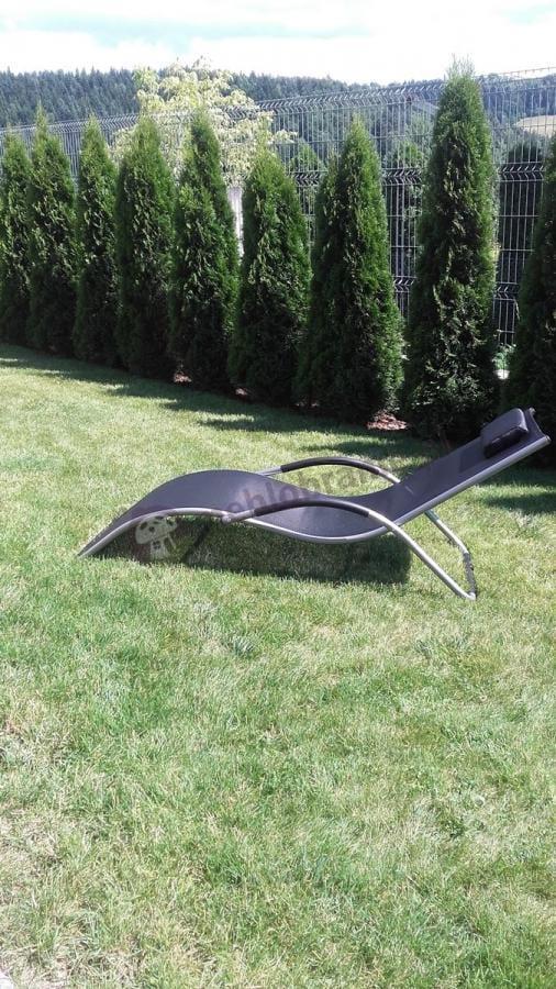 Czarny leżak ogrodowy ustawiony na trawniku