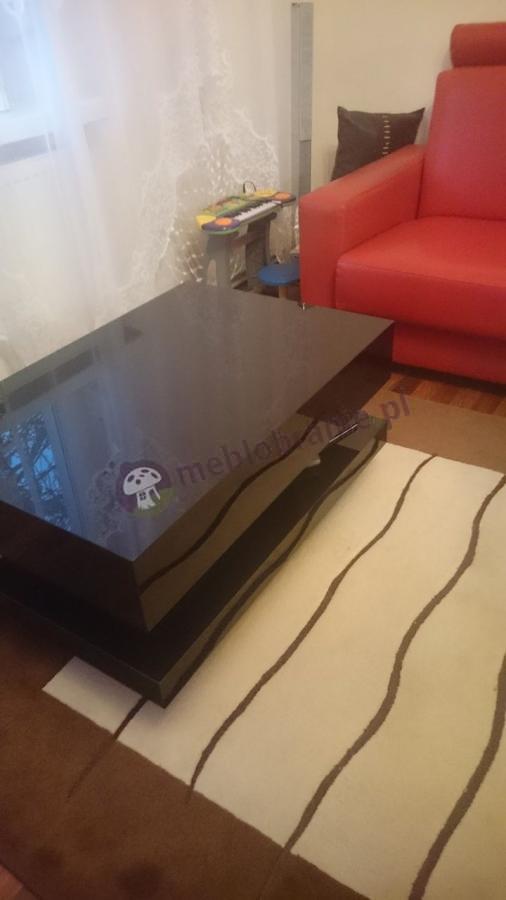 Czarny stolik kawowy do salonu ustawiony przy sofie