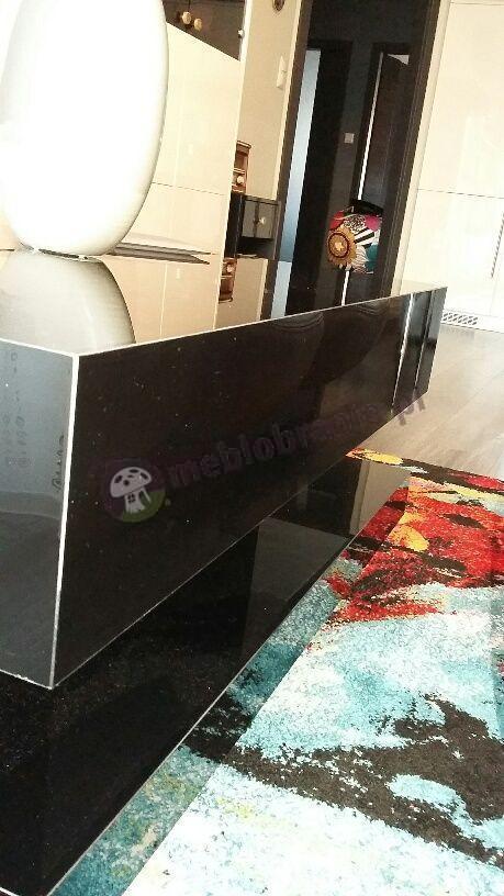 Czarny stolik kawowy ustawiony na kolorowym dywanie