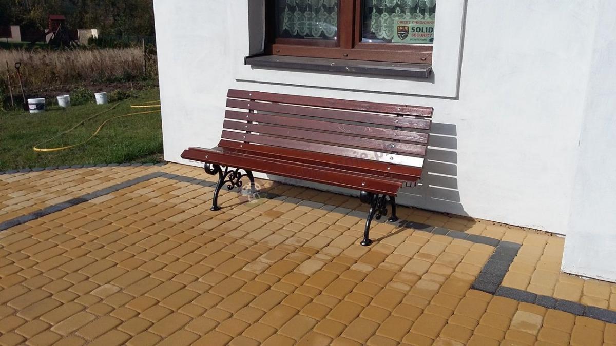 Drewniana ławka ogrodowa ozdobna ustawiona pod oknem