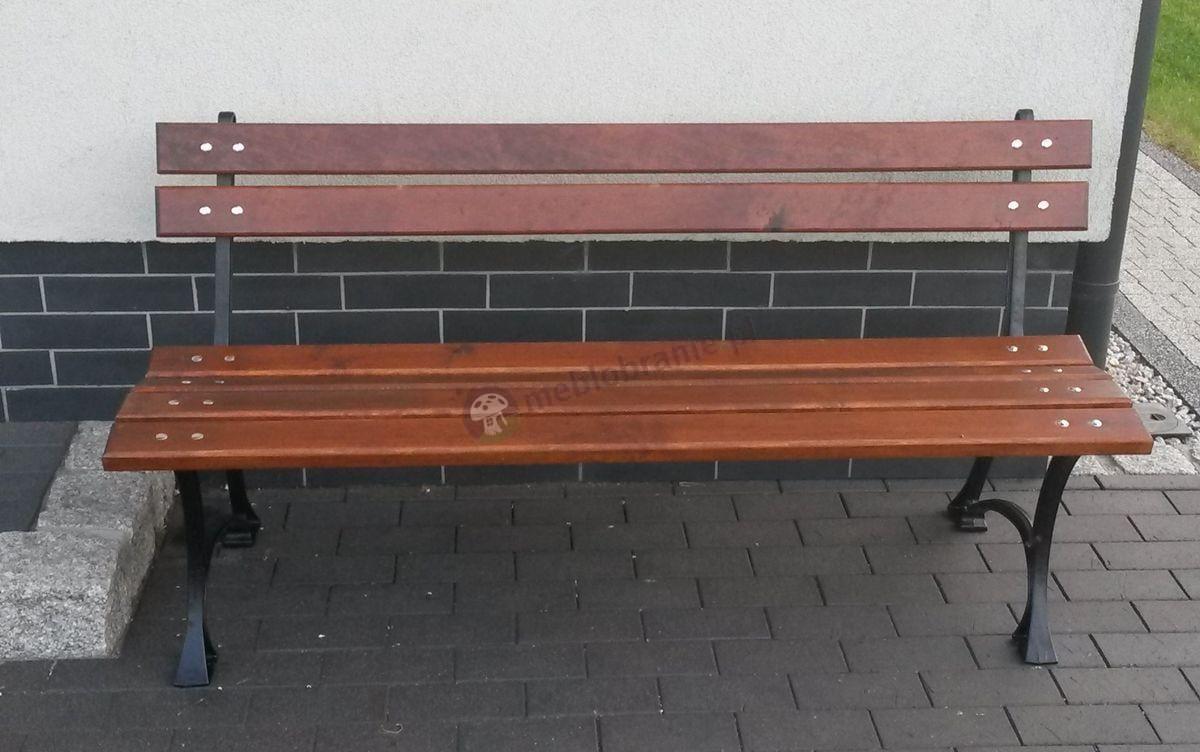 Drewniana ławka ogrodowa ustawiona pod budynkiem