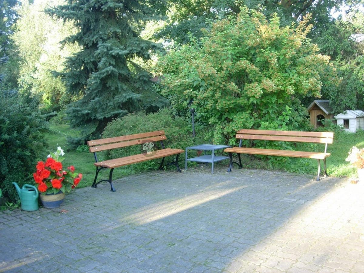 Drewniane ławki ogrodowe ustawione pod drzewami