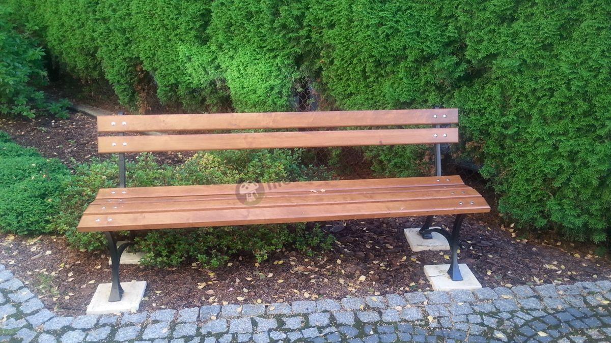 Duża ławka ogrodowa drewniana pod żywopłotem