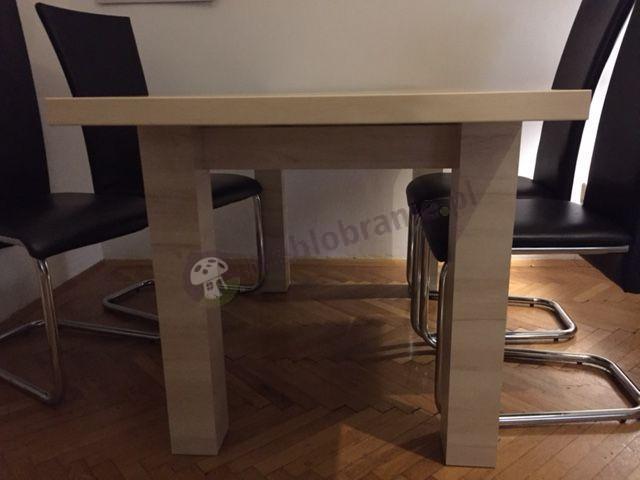 Duży stół rozkładany używany w salonie z nowoczesnymi krzesłami