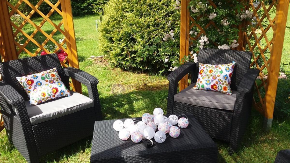 Fotele z kompletu Corfu Set przyozdobione jasnymi poduszkami w nasłonecznionym dużym ogrodzie