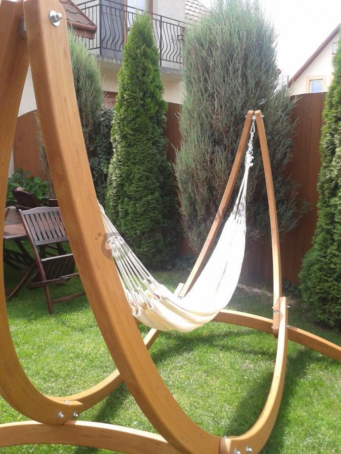 Hamak ogrodowy ze stelażem drewnianym w niewielkim ogrodzie