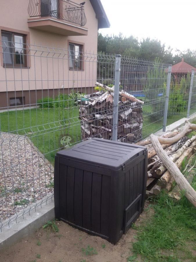 Kompostownik ogrodowy plastikowy ustawiony przed ogrodzeniem