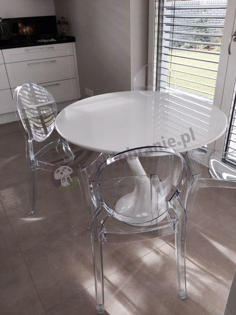 Krzesła plastikowe transparentne ustawione przy designerskim stoliku