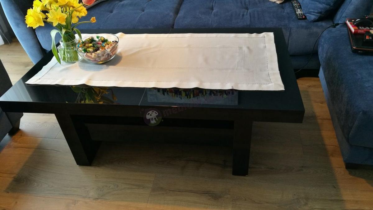 Ława czarna rozkładana do salonu nakryta białą serwetą