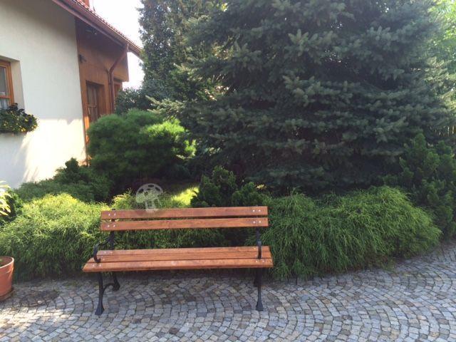 Ławka drewniana z oparciem używana w bujnym ogrodzie