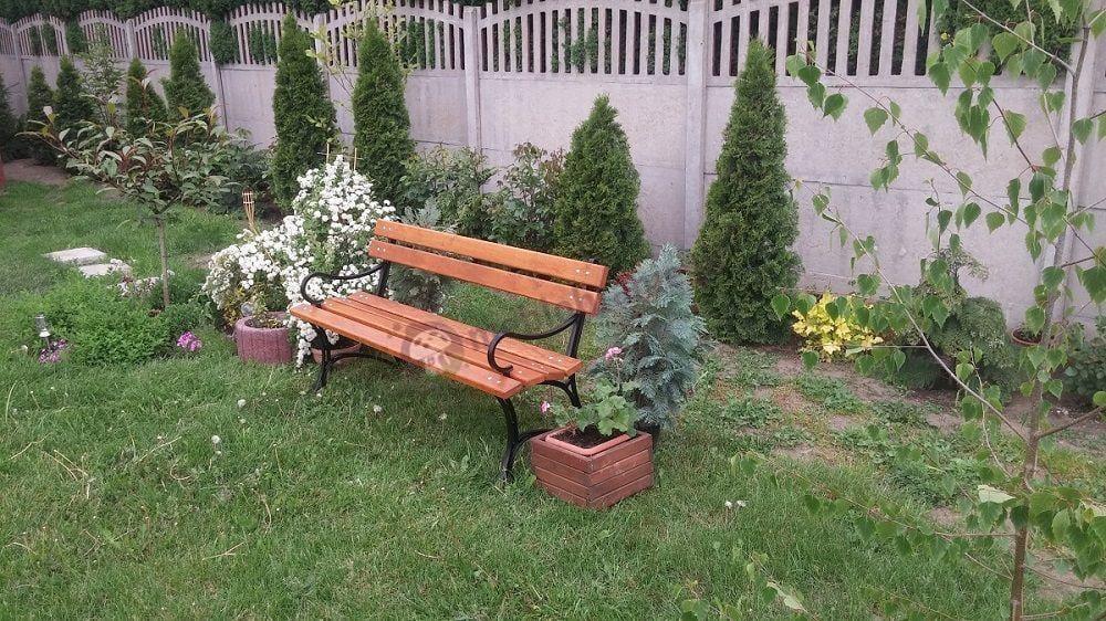 Ławka drewniana z podłokietnikami pośród bujnych roślin