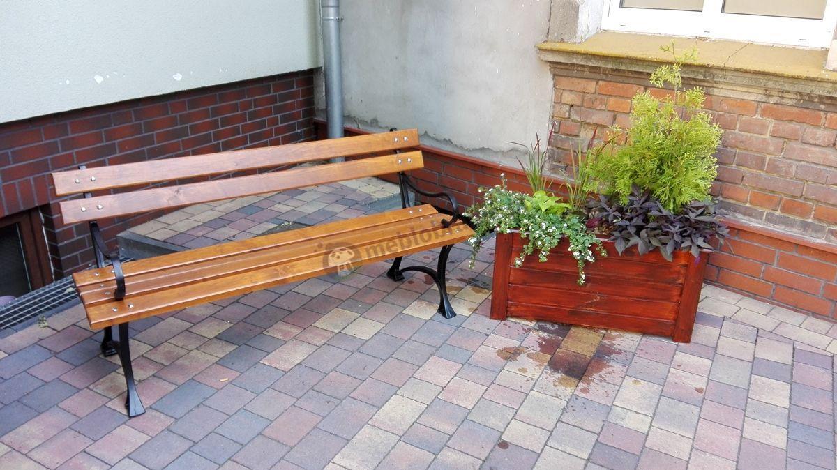 Ławka ogrodowa drewniana ozdobiona donicą z kwiatami