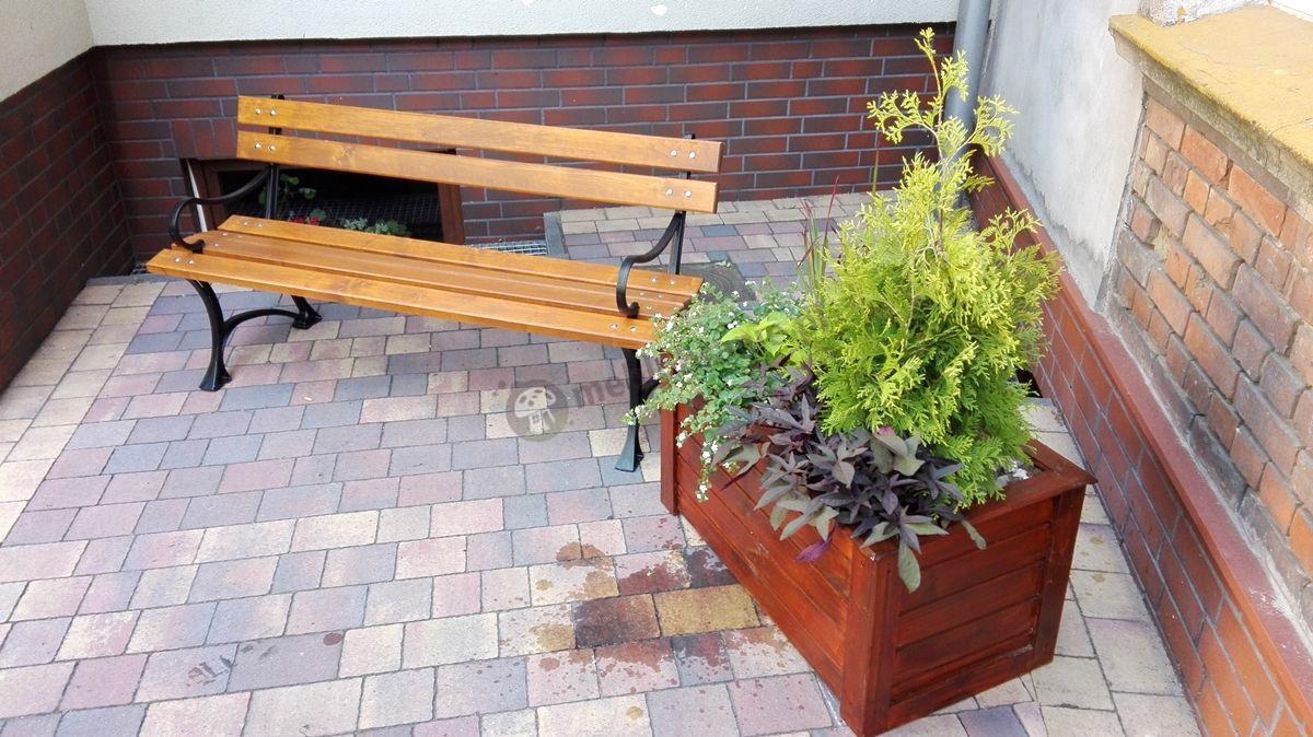 Ławka ogrodowa drewniana ustawiona w zaułku