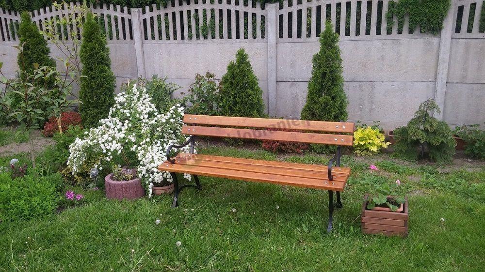 Ławka ogrodowa drewniana z podłokietnikami w ogrodzie