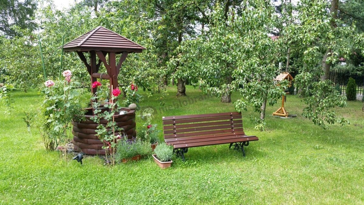 Ławka ogrodowa w otoczeniu studni oraz bujnej roślinności