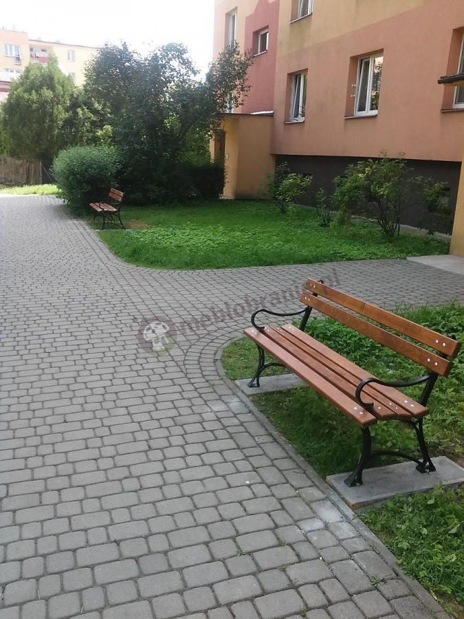 Ławki ogrodowe drewnianiane ustawione przed blokiem