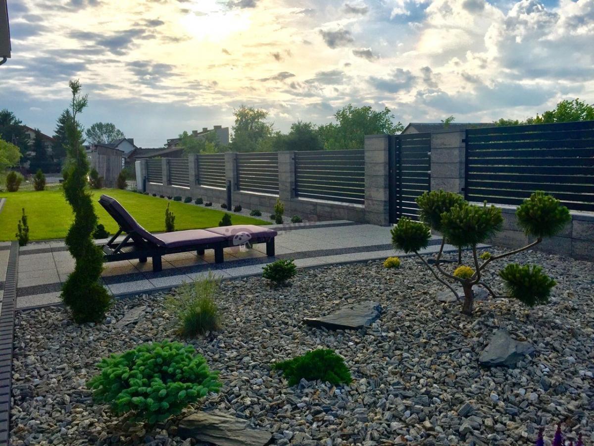 Leżak ogrodowy plastikowy w nowoczesnym przydomowym ogrodzie
