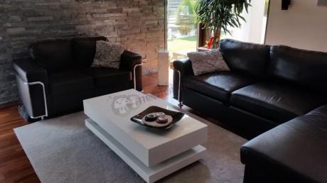 Biały stolik do salonu nowoczesny w otoczeniu ciemnych mebli