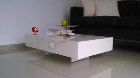 Biały stolik do salonu ozdobiony paterą z pralinkami