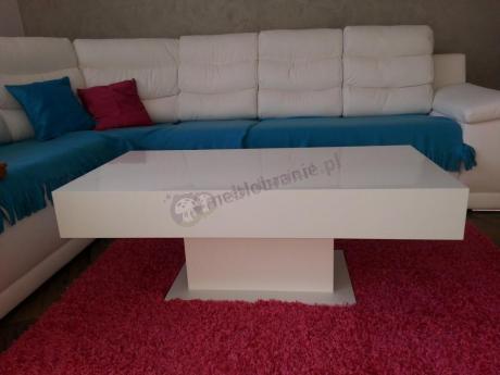 Biały stolik do salonu ustawiony na czerwonym dywanie