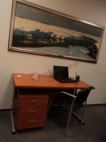 Biurko w komplecie z kontenerkiem ustawione pod obrazem