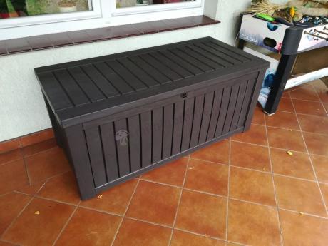 Brązowa skrzynia balkonowa Keter Rockwood Box ustawiona na tarasie