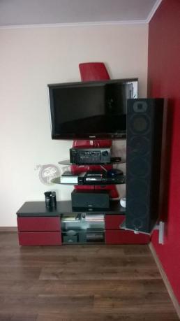 Czerwony panel pod telewizor wypełniony sprzętem elektronicznym