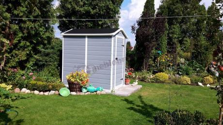 Domek do ogrodu umieszczony pośród uroczych rabatek