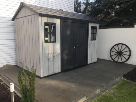 Domek narzędziowy Keter Oakland ustawiony w kącie ogrodu
