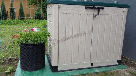 Doniczka cylindryczna ustawiona obok dużej szafy ogrodowej