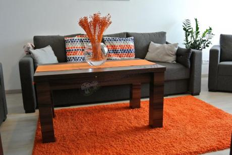 Drewnopodobna ława pokojowa uzupełniona pomarańczowymi dodatkami