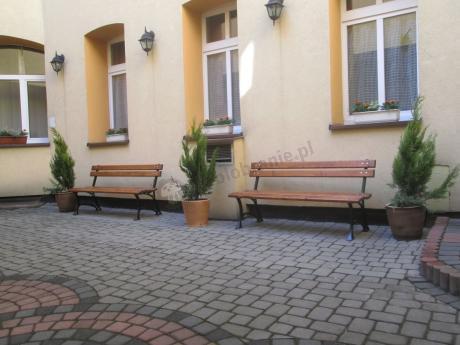 Ławki ogrodowe drewniane ustawione przy eleganckim bloku