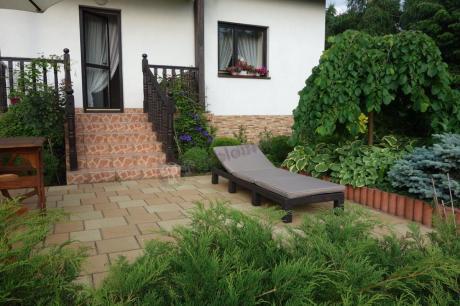 Leżak ogrodowy ustawiony w pełnym zieleni ogrodzie