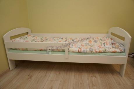 Łóżko dla dziecka z barierką przykryte kolorową kołdrą