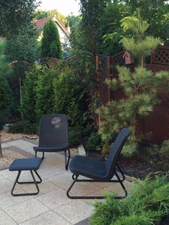 Meble rattan efekt pośród pięknego ogrodu