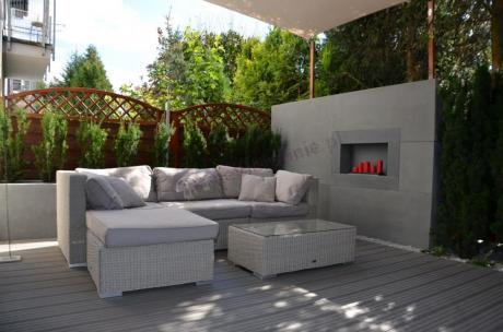 Modułowa sofa technorattan używana przy betonowej ścianie