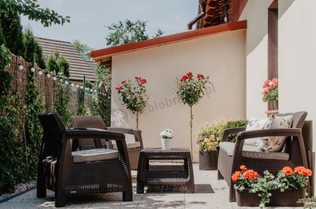 Ogrodowy komplet wypoczynkowy Corfu Set Max w otoczeniu kwiatów
