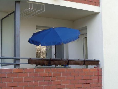 Parasol ogrodowy ustawiony na balkonie w bloku