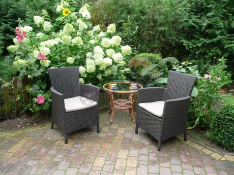 Plastikowe fotele ogrodowe Rattan Style Iowa w otoczeniu ogrodowej zieleni