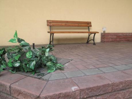 Ustawiona przy budynku ławka ogrodowa drewniana