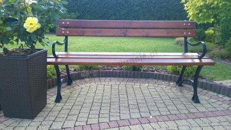 Wygodna żeliwna ławka ogrodowa ustawiona na kostce